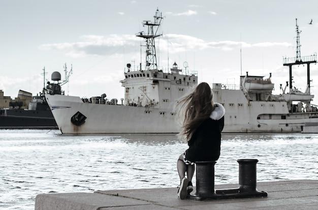 Jong meisje achteraanzicht kijken naar schepen. vrouw droomt van reizen over zee. langharige vrouw zittend op ligplaatsen, schepen op de achtergrond van de haven. eenzaamheid concept