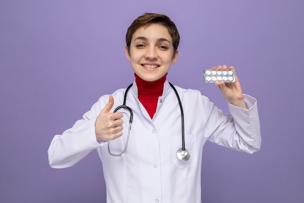 Jong meisje arts in witte jas met stethoscoop om nek met blister met pillen glimlachend vrolijk duimen opdagen staande op paars