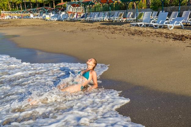 Jong meisje baadt in de golven van de middellandse zee