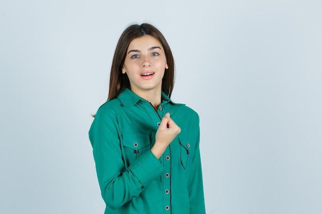 Jong meisje balde vuist over de borst in een groene blouse en ziet er vrolijk uit. vooraanzicht.