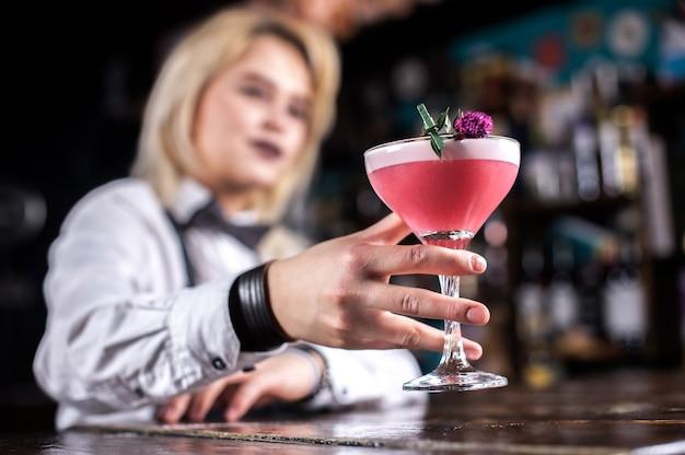 Jong meisje barman legt de laatste hand aan een drankje in de nachtclub