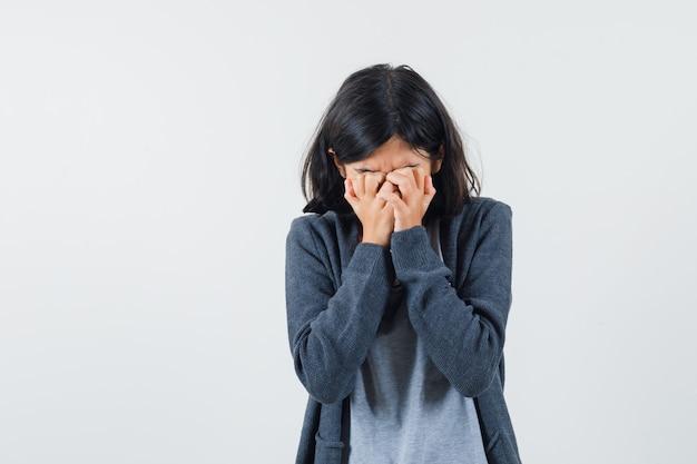 Jong meisje bedekt gezicht met handen in lichtgrijs t-shirt en donkergrijze hoodie met ritssluiting en kijkt verdrietig.