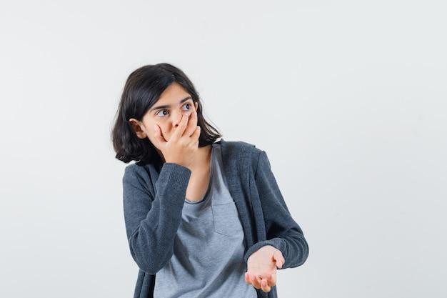 Jong meisje bedekt mond met hand in lichtgrijs t-shirt en donkergrijze hoodie met ritssluiting en kijkt verbaasd.