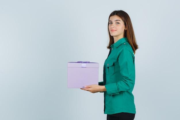 Jong meisje bedrijf geschenkdoos, camera in groene blouse, zwarte broek kijken en vrolijk kijken. vooraanzicht.