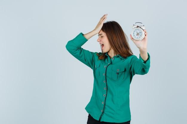 Jong meisje bedrijf klok, hand zetten hoofd in groene blouse, zwarte broek en op zoek gekwelde, vooraanzicht.