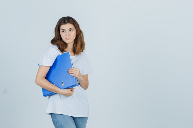 Jong meisje bedrijf map, wegkijken in wit t-shirt en op zoek dromerig, vooraanzicht.