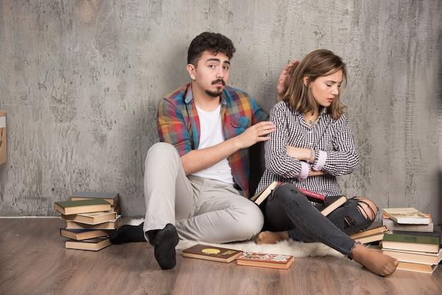 Jong meisje beledigd door man omringd door boeken
