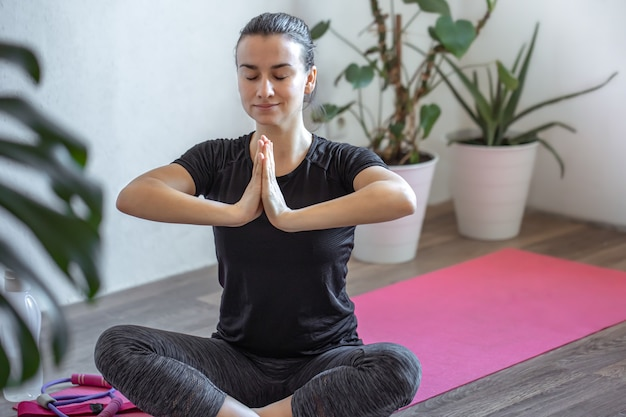 Jong meisje beoefent yoga thuis op de mat