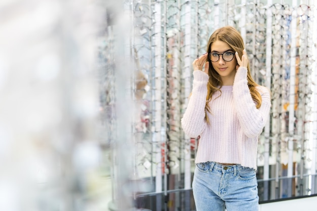 Jong meisje bereidt zich voor op haar studie en probeert een nieuwe bril voor haar perfecte look in de professionele winkel