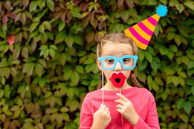 Jong meisje bereidt zich voor op verjaardagsfeestje met photo booth rekwisieten.