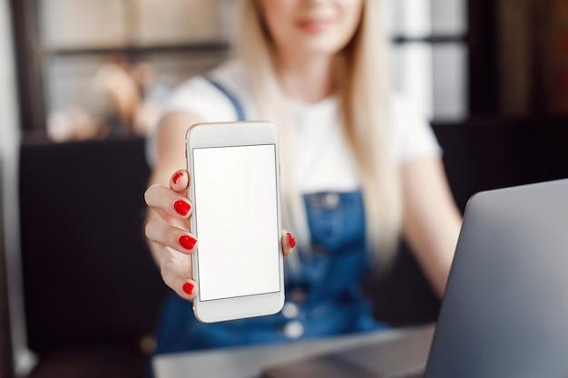 Jong meisje bij koffie het drinken koffie en het gebruiken van mobiele telefoon. online winkelen
