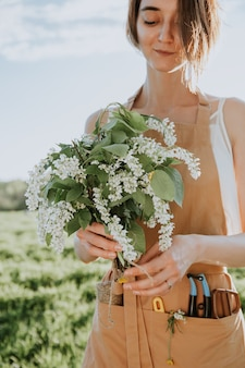 Jong meisje bloemist in schort maakt een bloemenboeket als een geschenk van bloeiende wilde bloemen bloemist op het werk kleine bedrijven bloemenwinkel vrouw met elegant boeket bloemen