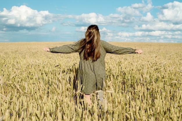 Jong meisje danst in een tarweveld. gaat met zijn hand over de oren. staat met zijn rug. haar dat in de wind vliegt, levensstijl.