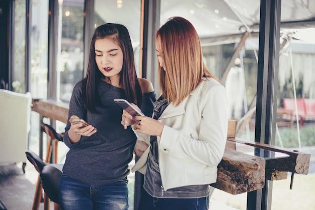 Jong meisje dat aan de telefoon van haar vriend kijkt en opwindend en glimlachend voelt