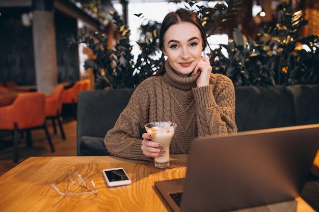 Jong meisje dat aan een computer in een koffie werkt