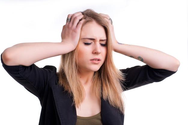 Jong meisje dat aan hoofdpijn op een witte achtergrond lijdt