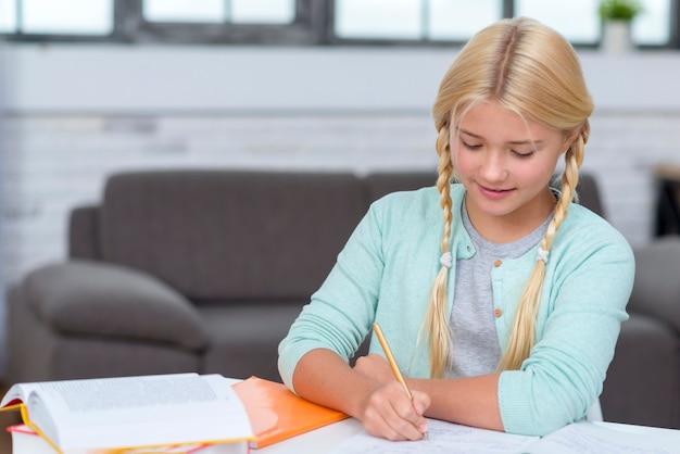 Jong meisje dat aantekeningen maakt op haar notitieboekje