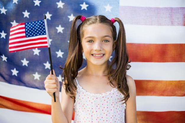 Jong meisje dat amerikaanse vlag houdt