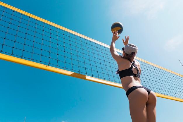 Jong meisje dat beachvolleybal speelt. beachvolleybal kampioenschap. de vrouw reikt naar de bal. een gele volleybal over het net gooien. overwinningspunt. buitensport spellen.