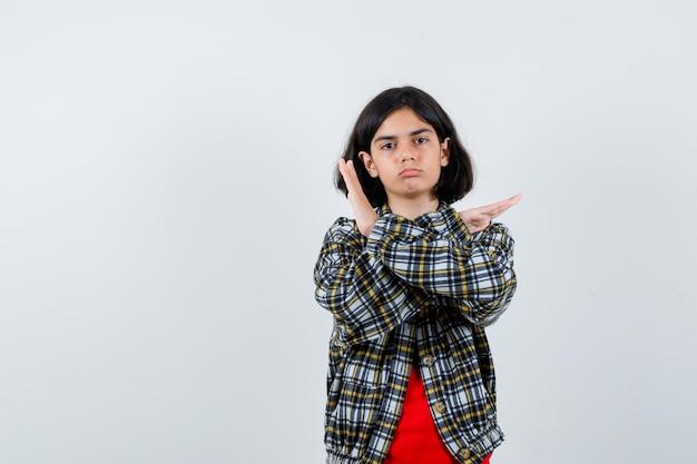 Jong meisje dat beperkingsgebaar in geruit overhemd en rood t-shirt toont en er schattig uitziet, vooraanzicht.