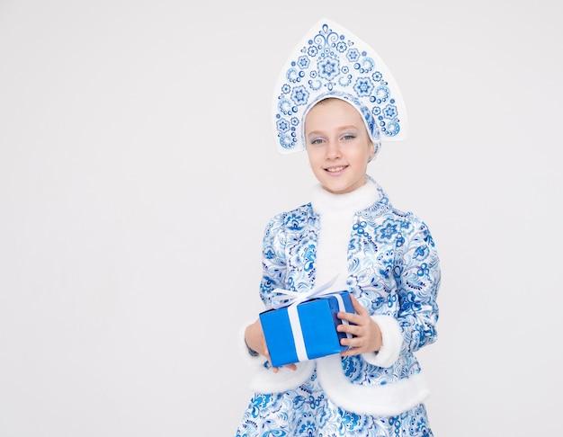 Jong meisje dat blauw pak van de doos van de de holdingsgift van het sneeuwmeisje draagt