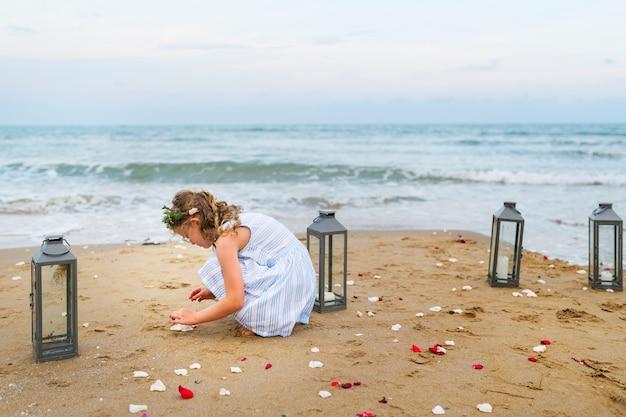 Jong meisje dat bloembloemblaadjes op het strand verzamelt