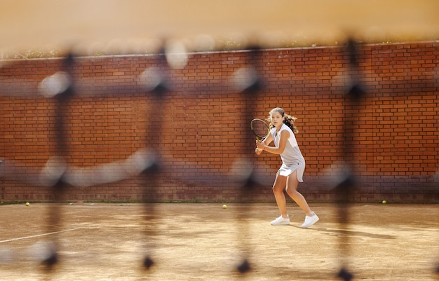 Jong meisje dat de bal met het tennisracket blokkeert tijdens de training