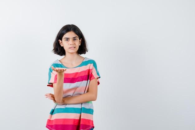 Jong meisje dat de hand uitrekt als iets in een kleurrijk gestreept t-shirt en er serieus uitziet. vooraanzicht.