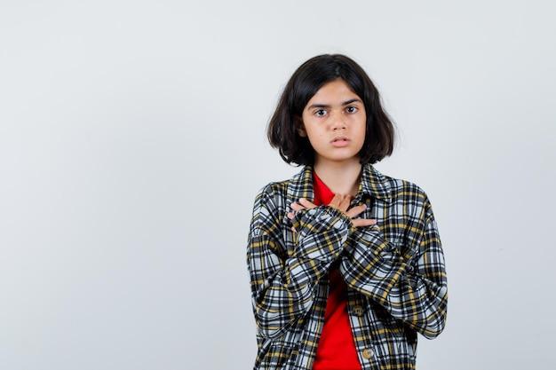 Jong meisje dat de handen op de borst rust in een geruit overhemd en een rood t-shirt en er serieus uitziet. vooraanzicht.