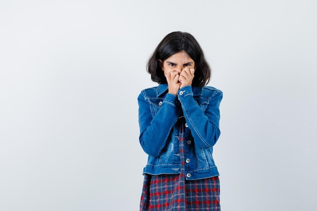 Jong meisje dat de handen op de mond zet in een geruit overhemd en een spijkerjasje en er serieus uitziet. vooraanzicht.