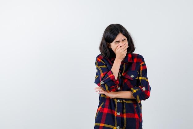 Jong meisje dat de mond bedekt met de hand, de hand op de elleboog houdt in een geruit overhemd en er geïrriteerd uitziet, vooraanzicht.