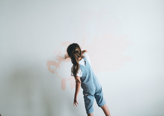 Jong meisje dat de muren roze schildert