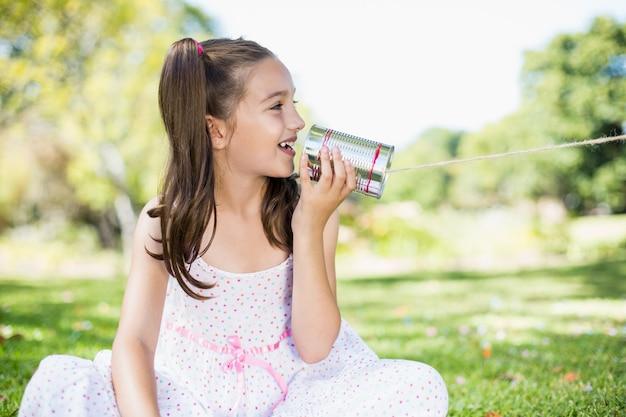 Jong meisje dat door de telefoon van het tinblik spreekt