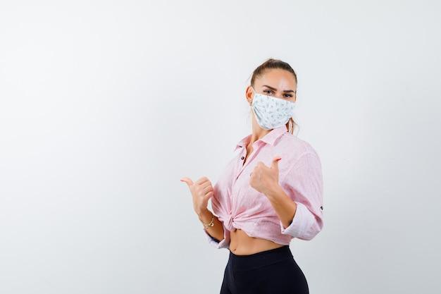Jong meisje dat dubbele duimen in roze blouse, zwarte broek, masker toont en gelukkig, vooraanzicht kijkt.