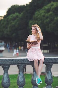 Jong meisje dat een boek in het park leest.