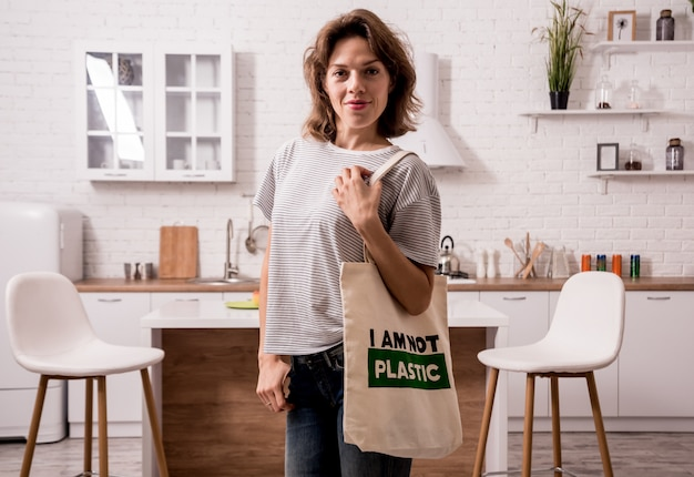 Jong meisje dat een doekzak houdt. bij de keuken. ik ben geen plastic.
