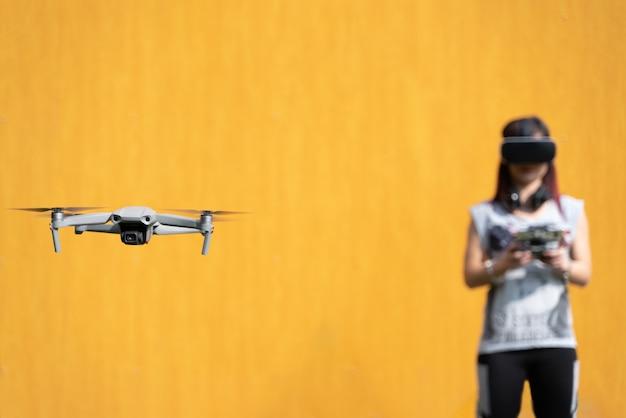 Jong meisje dat een drone vliegt met een vr-bril op een gele achtergrond