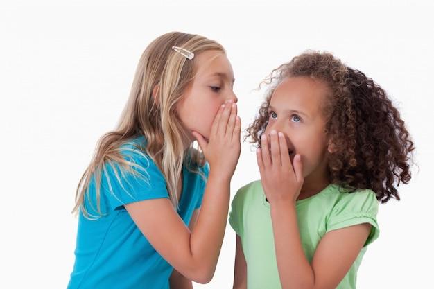 Jong meisje dat een geheim fluistert aan haar vriend