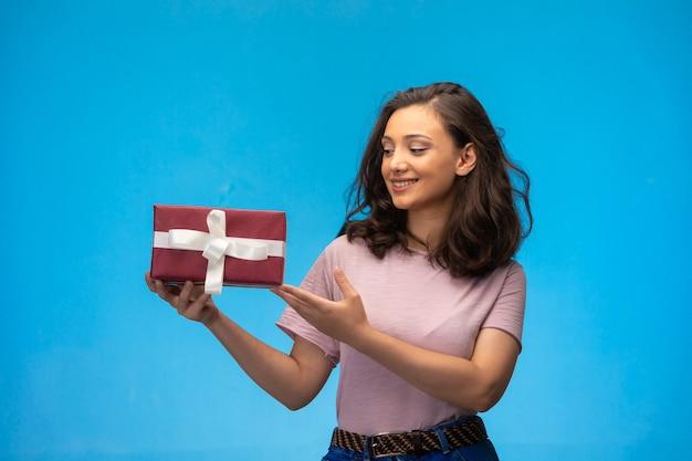 Jong meisje dat een geschenkdoos houdt en lacht terwijl u ernaar kijkt.