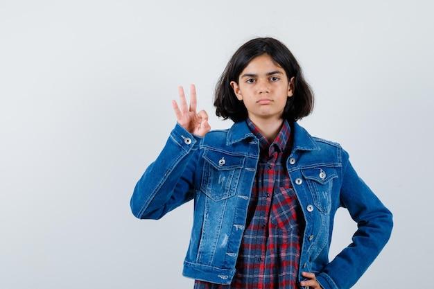 Jong meisje dat een goed teken toont terwijl ze de taille in een geruit overhemd en een spijkerjasje op de taille legt en er serieus uitziet, vooraanzicht.
