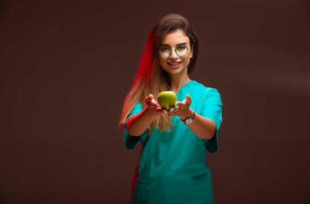 Jong meisje dat een groene appel in de hand aanbiedt.