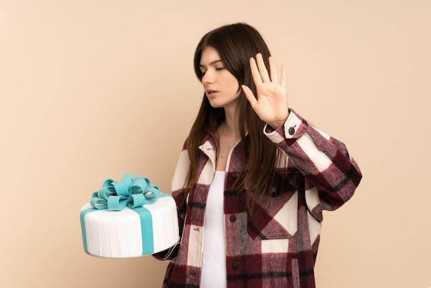 Jong meisje dat een grote cake houdt die op beige wordt geïsoleerd die eindegebaar maakt en teleurgesteld