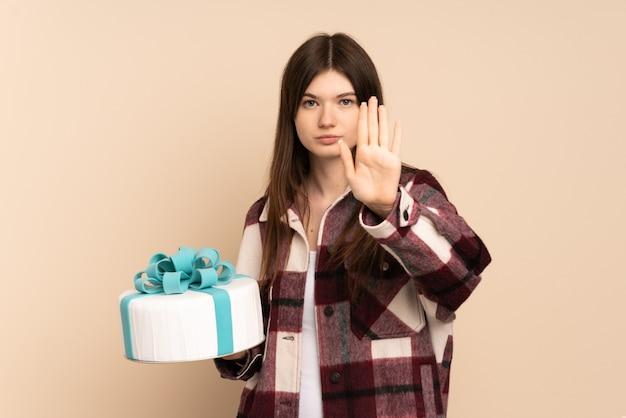 Jong meisje dat een grote cake houdt die op beige wordt geïsoleerd die stopgebaar maakt