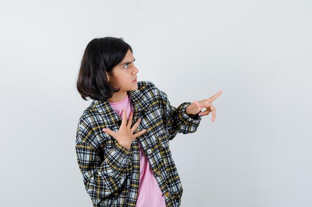 Jong meisje dat een hand op de borst legt terwijl ze een andere hand naar rechts uitstrekt in geruit overhemd en roze t-shirt en er gefocust uitziet, vooraanzicht.