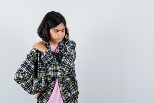 Jong meisje dat een hand op de schouder legt terwijl ze een andere hand op de taille houdt in een geruit overhemd en een roze t-shirt en er uitgeput uitziet, vooraanzicht.