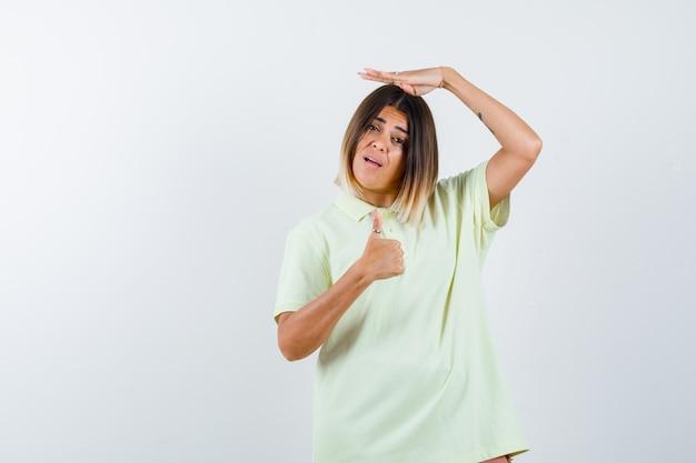 Jong meisje dat één hand op hoofd houdt, duim in t-shirt toont en gelukkig, vooraanzicht kijkt.