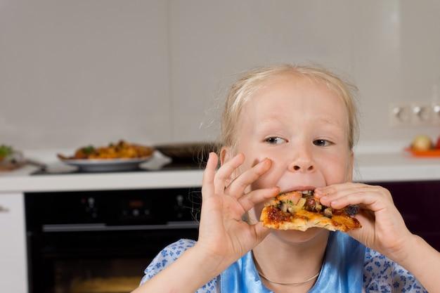 Jong meisje dat een hap van zelfgemaakte italiaanse pizza neemt en zijwaarts kijkt terwijl ze hongerig van haar maaltijd geniet