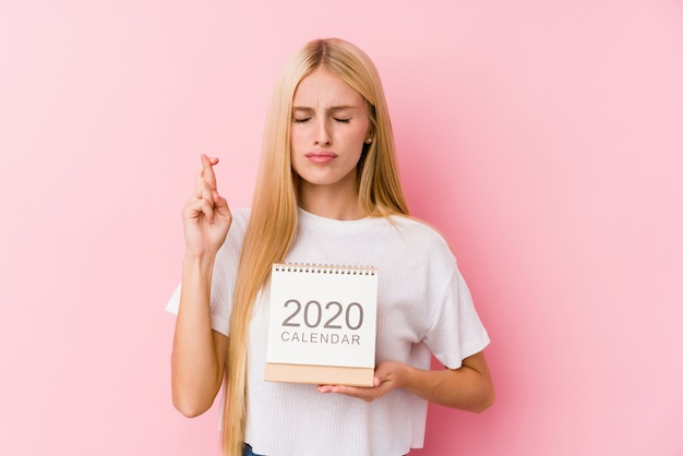 Jong meisje dat een kalender van 2020 houdt die vingers kruist voor het hebben van geluk