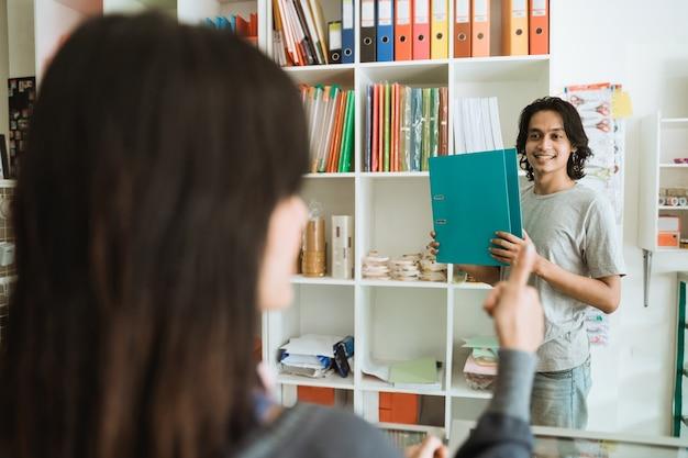 Jong meisje dat een kantoorbehoeftenwinkel bezoekt die punt kiest dat duimen toont