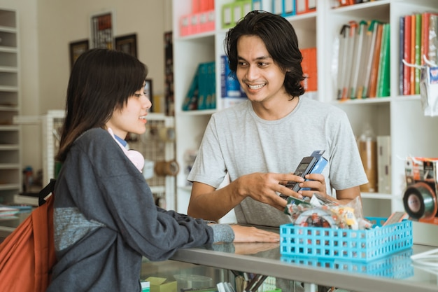 Jong meisje dat een kantoorboekhandel bezoekt, praat met de mannelijke kassier over prijzen
